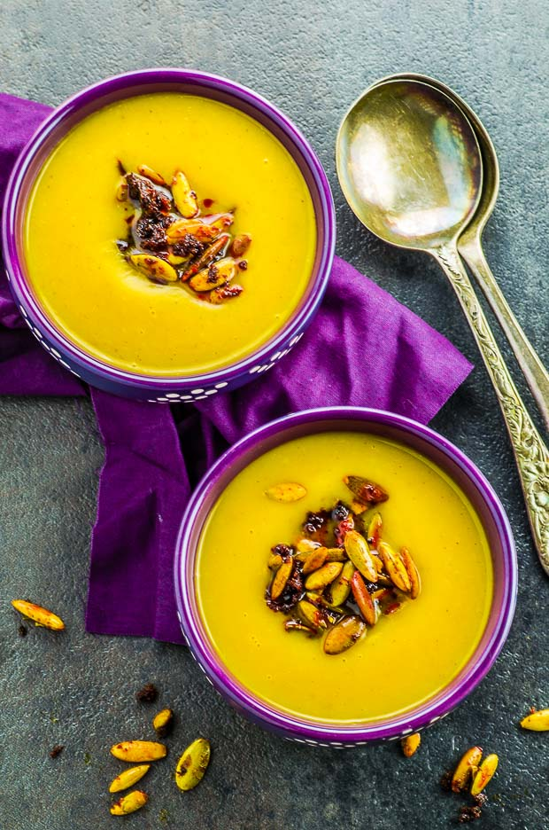 Birds eye view of two purple and white polkadot bowls filled with roasted butternut squash soup, topped with spiced pumpkin seeds, on a purple napkin. Two spoons are placed on the right hand sides of the bowls with a few spiced pumpkin seeds scattered