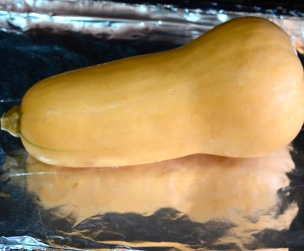 Whole butternut squash on a foil lined baking sheet