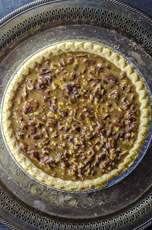 An unbaked pie crust filled with bgourbon pecan pie fill-in