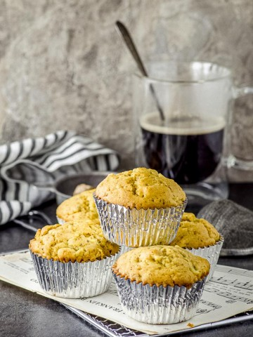 five ginger turmeric pear muffins stacked on a white plate