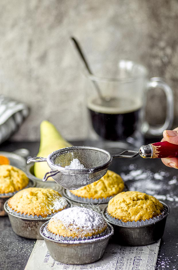 Sprinkling powdered sugar on Ginger, Pear & Turmeric Muffins