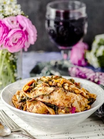 Close up view of a table setting with a bowl of tagliatelle with mushroom ragu, a glass of red wine and a vase with pink flowers