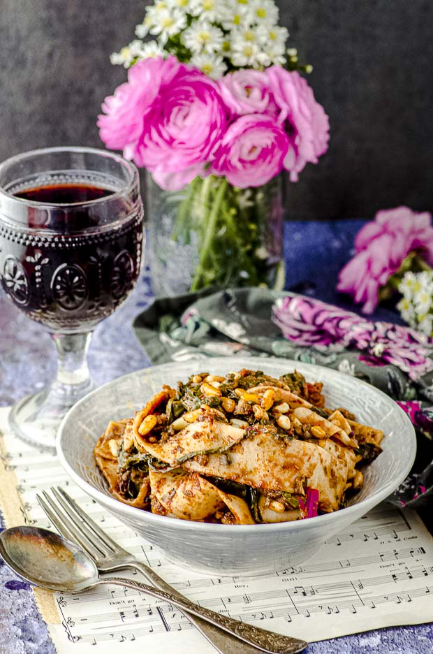 Side view of a table setting with a bowl of tagliatelle with mushroom ragu, a glass of red wine and a vase with pink flowers