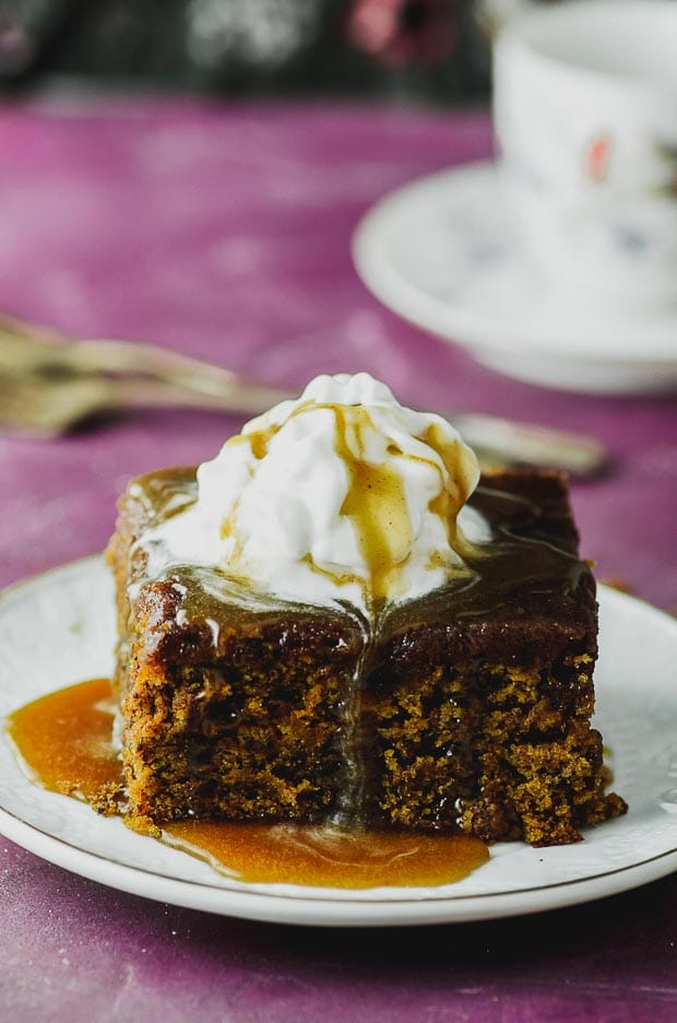 A close up on a vegan sticky toffee pudding topped with whipped cream