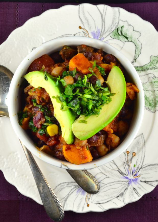 Bird's eye view of a white bowl with printed flower full of three bean and sweet potato chili placed on a white plated printed with flowers. The chili is topped with sliced avocado and cilantro