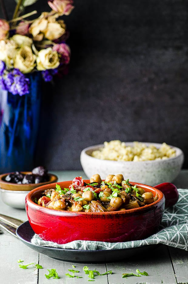 Side view of a red stone wear bowl with fennel and chickpea stew with a bowl of quinoa in the background