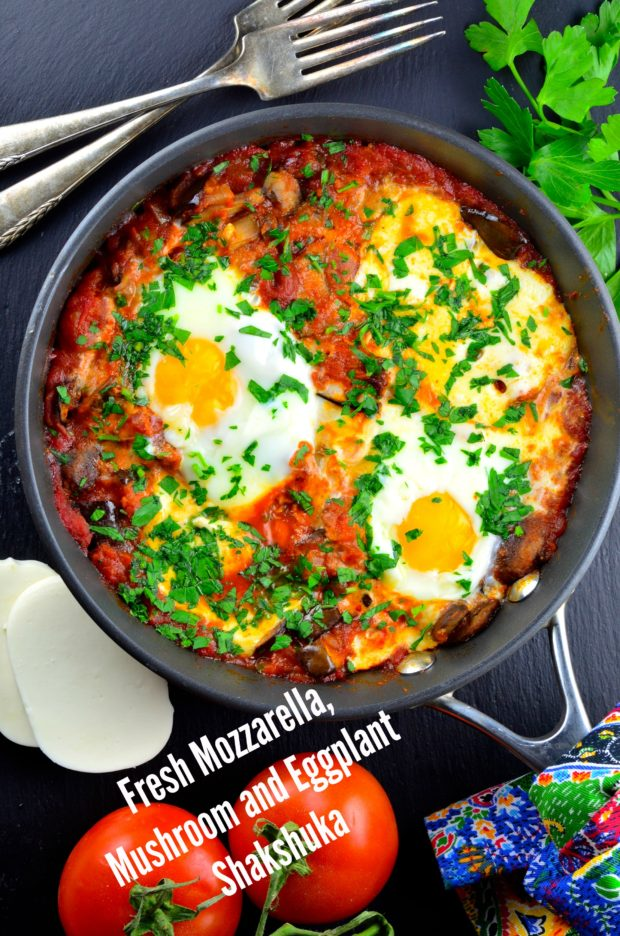 Vegetarian Passover Recipes: A Bird's eye view of a pan of Fresh Mozzarella, Mushroom and Eggplant Shakshuka, in a rich tomato sauce, with 2 eggs on top and generously sprinkled with chopped parsley. On the table surface there are 2 silver forks, a bunch of cilantro, 2 fresh tomatoes and 2 slices of fresh mozzarella.