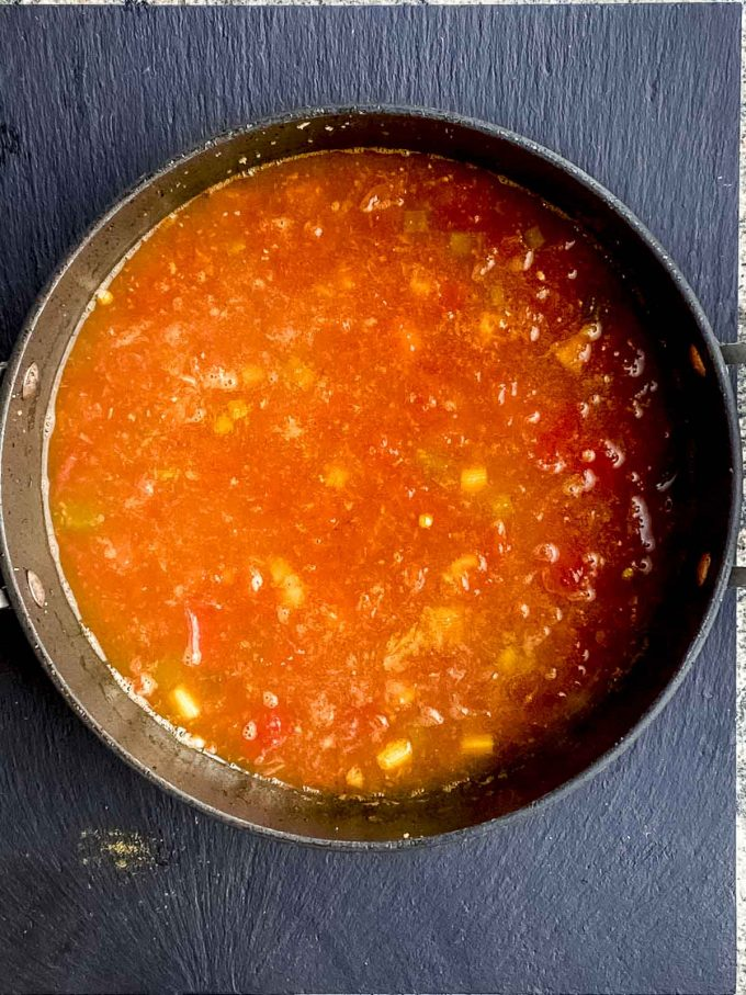 Adding water to the tomato base for lentil curry