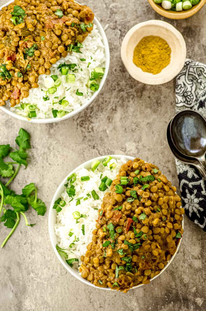 birds' eye view of two bowls filled with white rice and lentil curry.