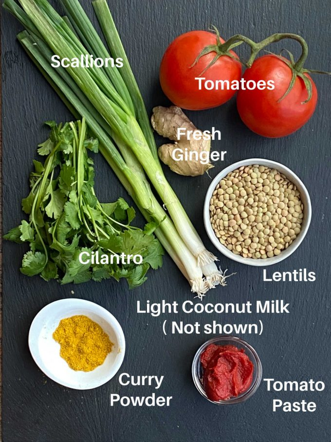 Lentil curry ingredients labeled. Tomatoes, fresh ginger, scallions. tomato paste, curry powder, cilantro, lentils, light coconut milk