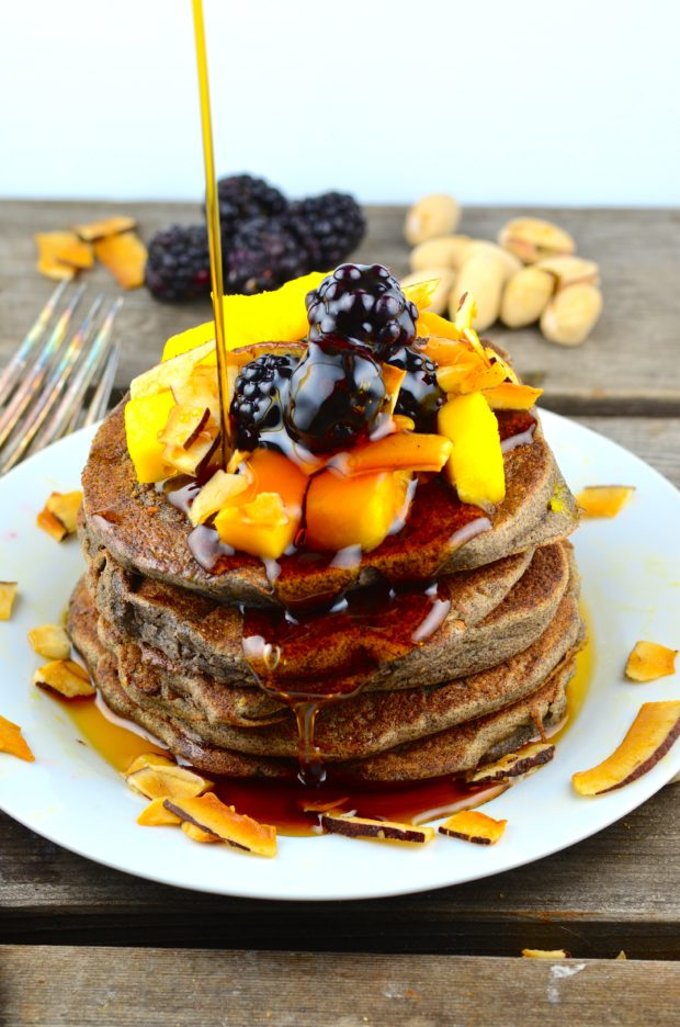 A stack of Buckwheat & Pistachio Pancakes (Vegan & Gluten Free), topped with fresh diced mango, blackberries , coconut chips and maple syrup.
