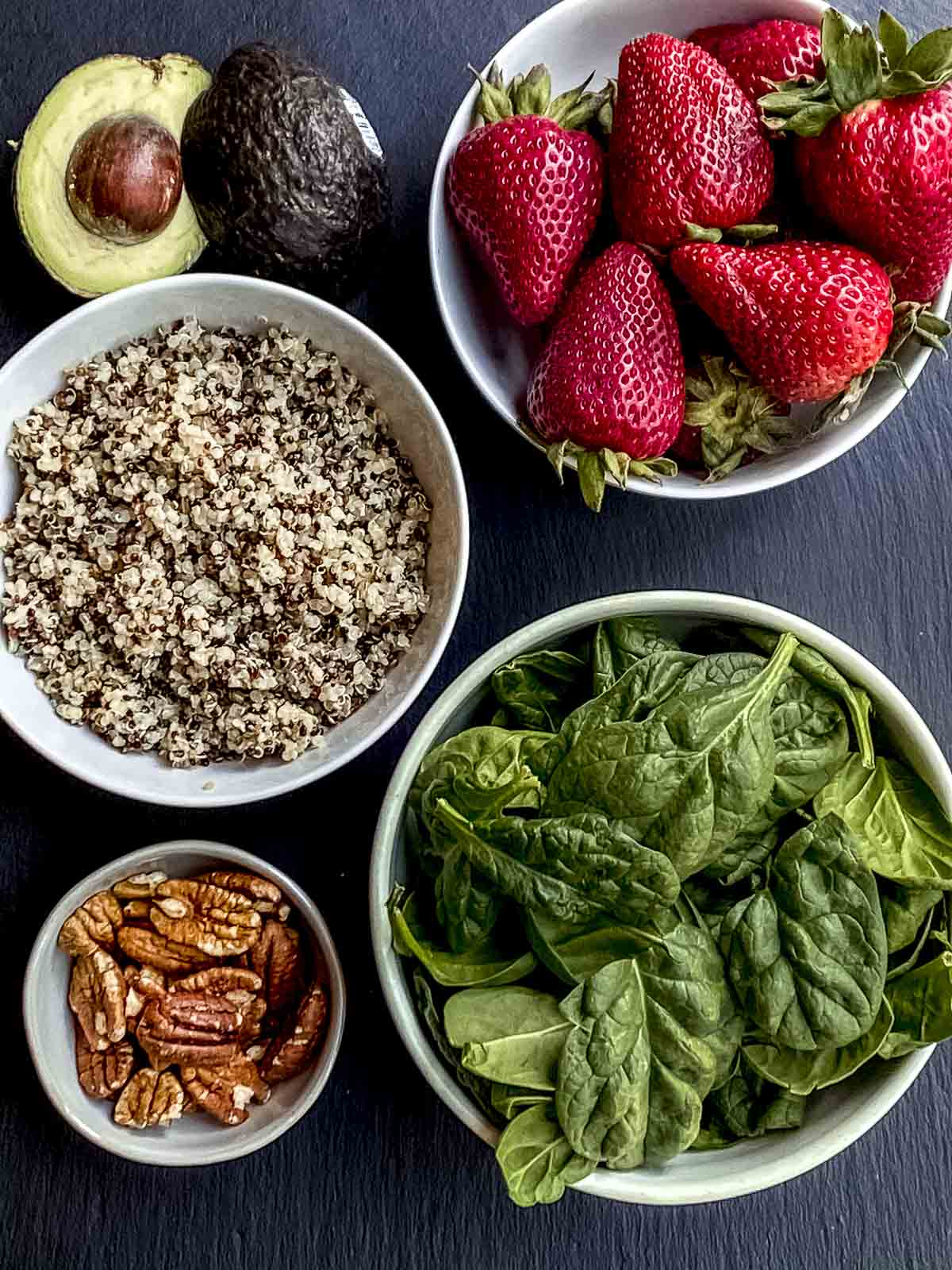 Ingredients to make spinach salad: strawberries, quinoa. avocado, pecans, spinach