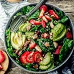 bird's eye view of a plate of spinach salad with strawberries, avocado, and candied pecans