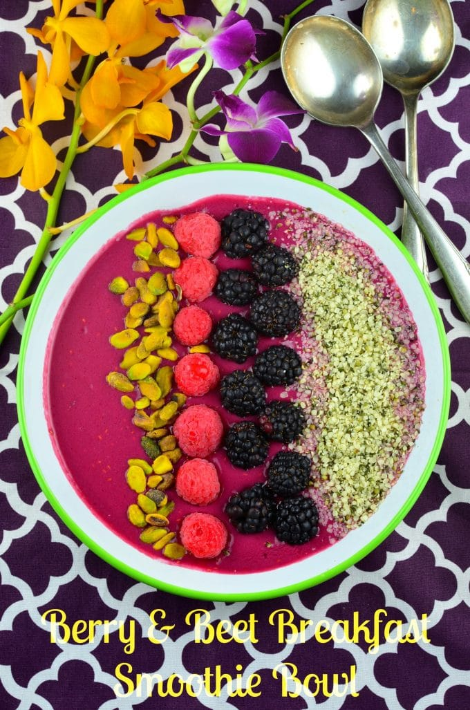 Bird's eye view of a magenta smoothie bowl topped with pistachios, raspberries, blackberries, and hemp seeds