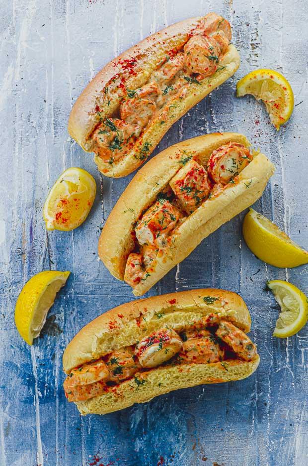 Three vegan lobster rolls on a blue surface