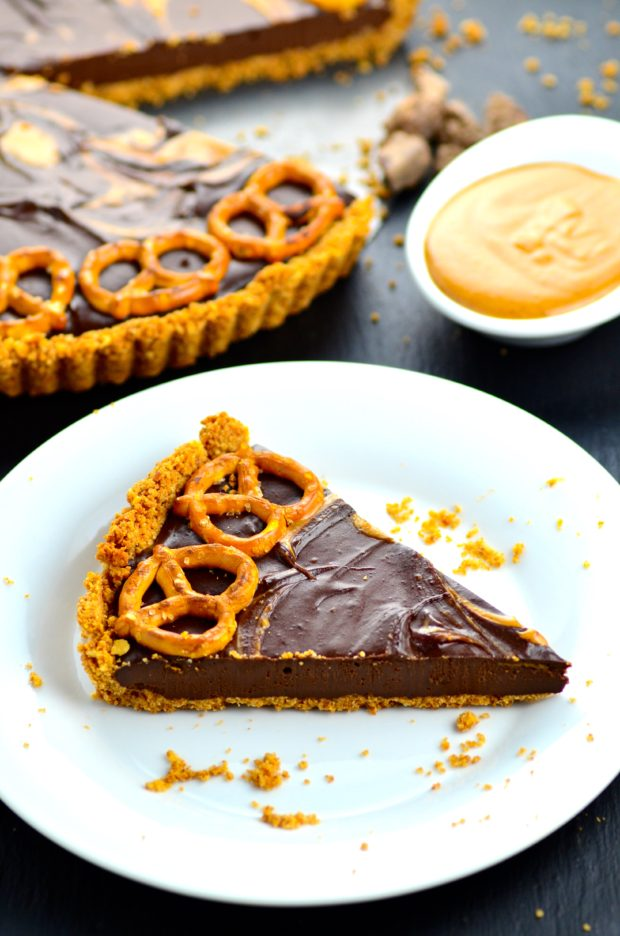 a slice of Vegan and Gluten Free Chocolate Peanut Butter Tart with crunchy salty Pretzels on a white plate. The full tart with a slice missing is on the background and a small white bowl with peanut butter is set on the background as well.