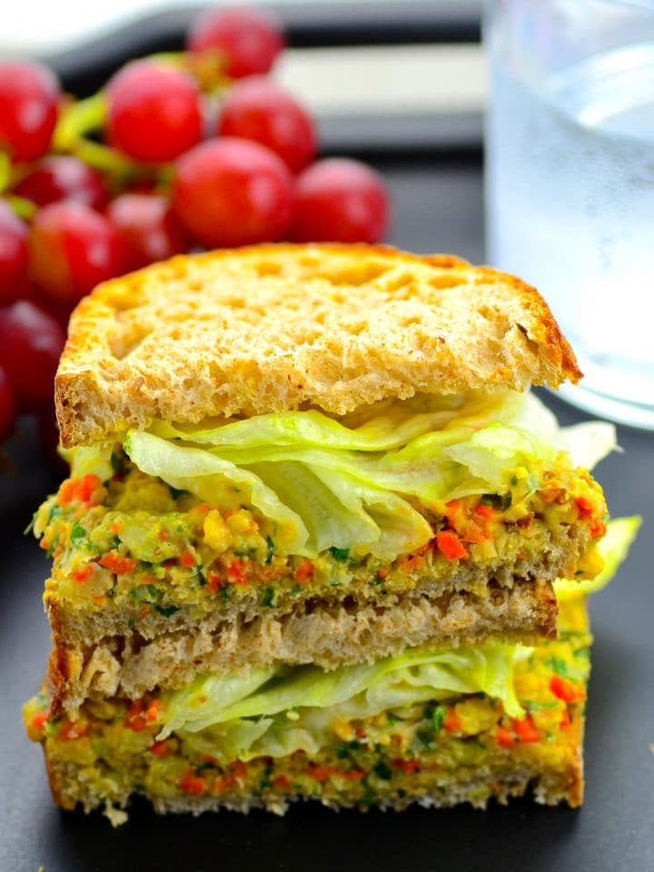 Side view of a smashed chickpea salad sandwich with grapes in the background