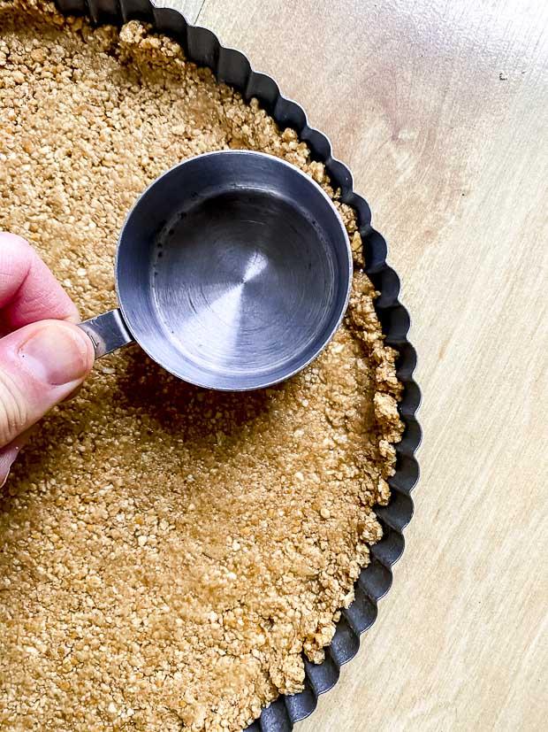 pressing pretzel crust into a tart pan