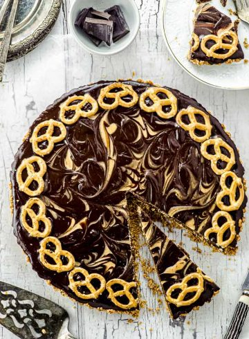 Bird's eye view of a whole pretzel chocolate peanut butter tart with a slice cut up