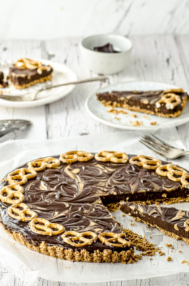 Side view of a chocolate peanut butter tart with pretzel crust with two slices on two white plates in the background