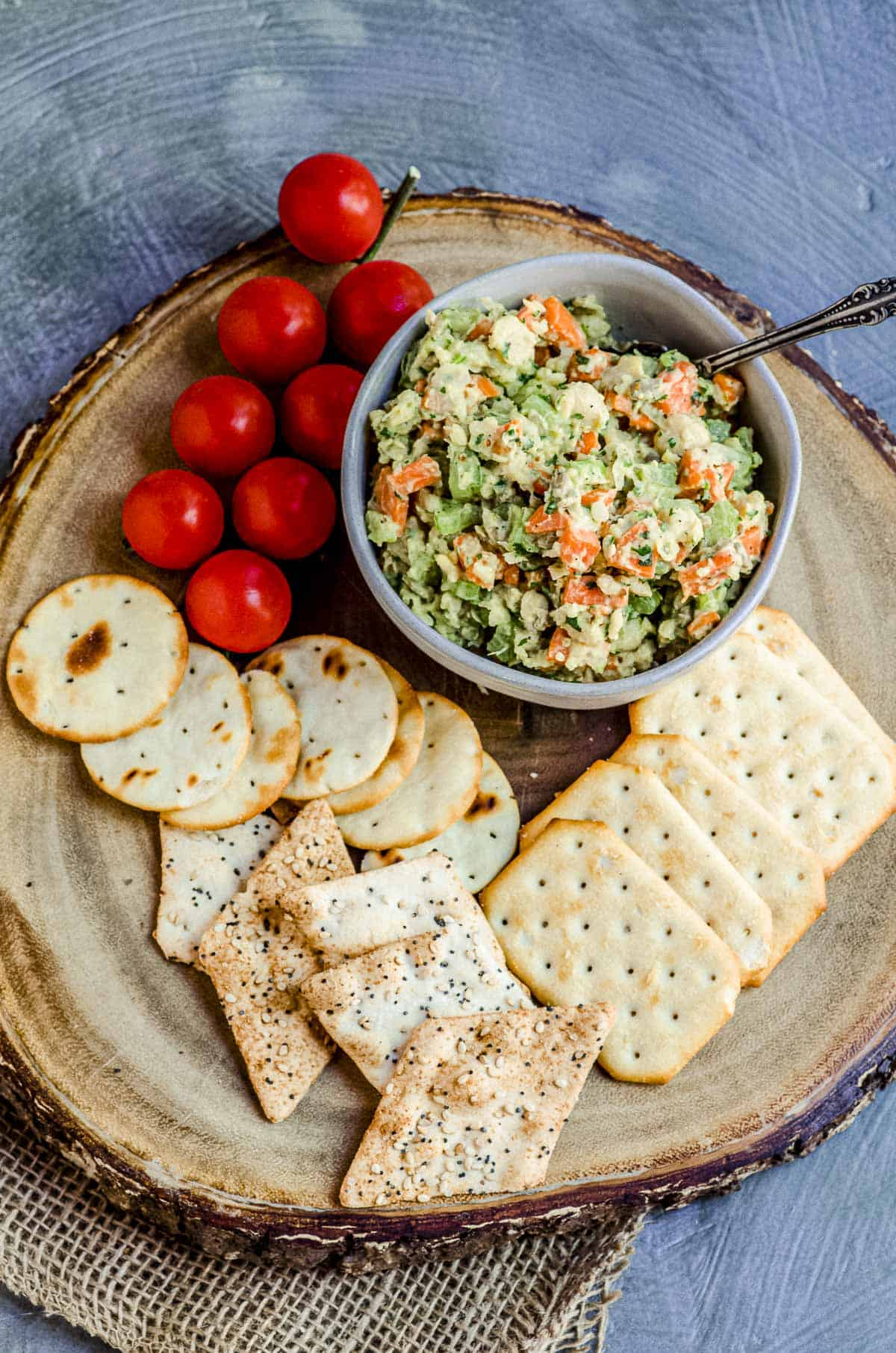 Close up view of a bowl with chickpea salad on a wood board with assorted crackers and fresh cherry tomatoes