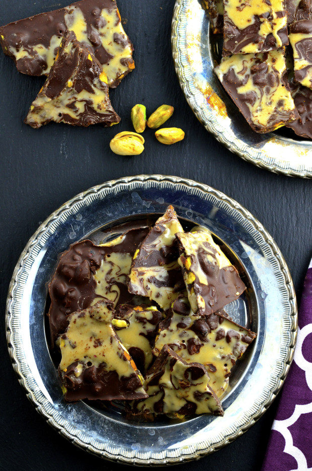 chocolate bark with pistachios on two silver plates