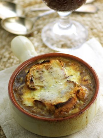 A vegetarian French onion soup in a beige terra-cotta bowl with an earthy brown rim. On the background there is a cup of red wine.