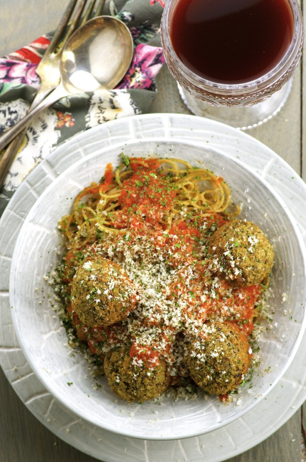 Birds eye view of a grey bowl of spaghetti and vegan meatballs placed on a grey plate. Everything is on top of a grey wooden surface with a grey napkins with printed pink and white flowers and a glass of wine