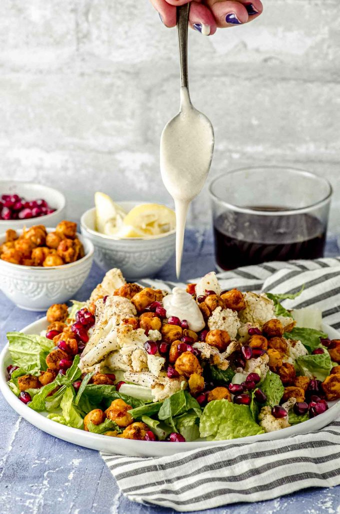 Drizzling tahini dressing on a roasted cauliflower salad with spiced chickpeas