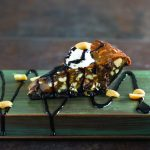 a slice of chocolate chip peanut pie with chocolate drizzle on a green wood plank