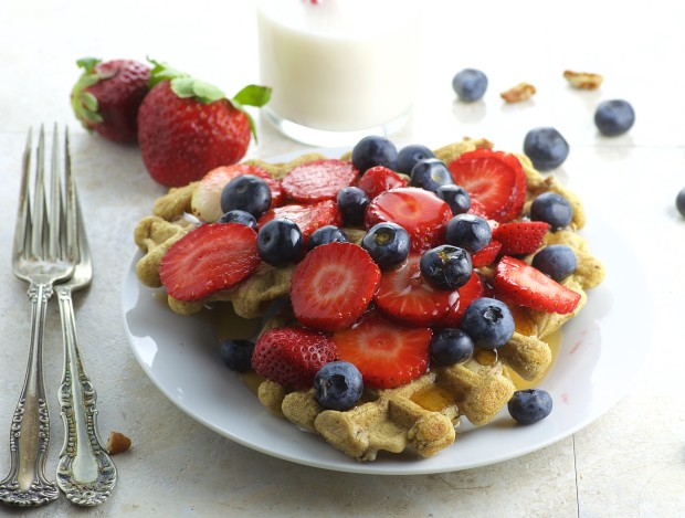 Side view of maple pecan waffles with fresh strawberries and blueberries piled on top