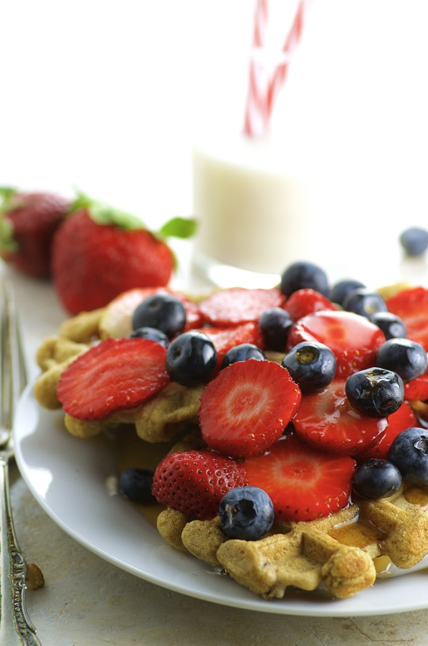 Close-up view of Two maple pecan waffles with a pile of sliced strawberries and fresh blueberries with a glass of milk in the background.