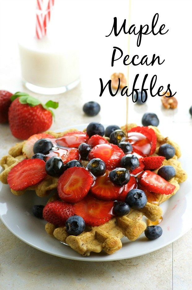Two maple pecan waffles with a pile of sliced strawberries and fresh blueberries with a glass of milk in the background.