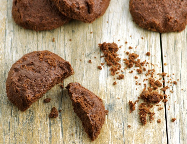 Close up of a broken vegan flouress chocolate cookie, some cookie crumbs and three whole cookies on wooden surface.