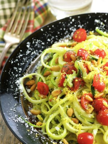 Partial side view of a dark plate filled with zucchini noodles and topped with parmesan cheese, grape tomatoes and pesto