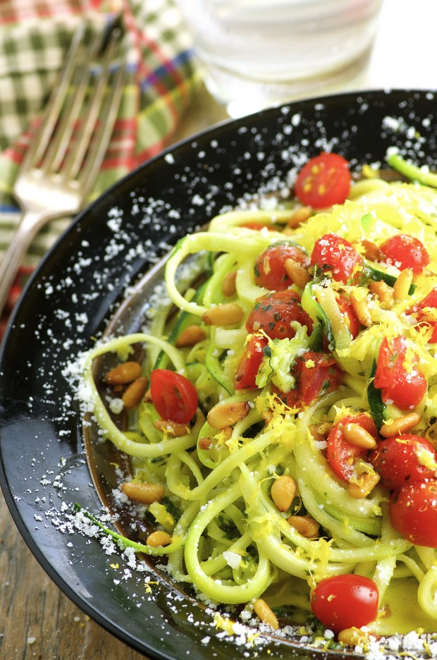 Close up view of a plate full of zucchini noodles with fresh tomatoes and pine nuts