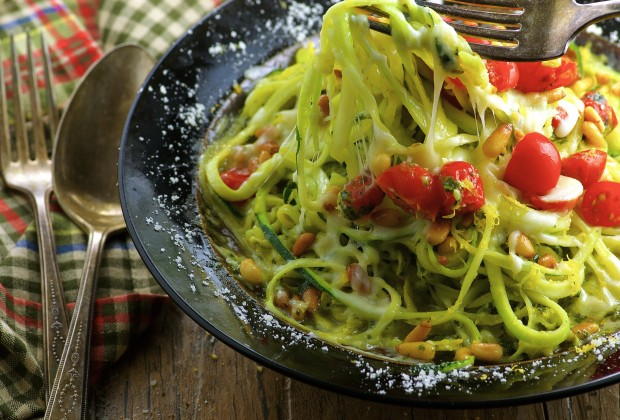 Cheesy Passover Pesto Zoodles ( Zucchini Pasta) , this low carb, gluten free vegetarian recipe features yellow and green zucchini pasta, basil parmesan pesto, creamy mozzarella, fresh tomatoes and pine nuts.