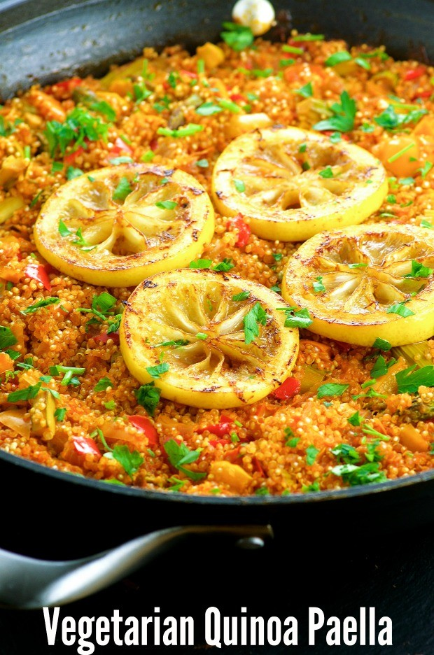 Close up of the Vegan Gluten Free Quinoa Paella garnished with four slices of roasted lemon in a paella pan