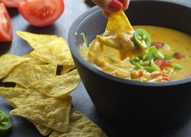 Dipping a tortilla chip into a bowl of vegan queso