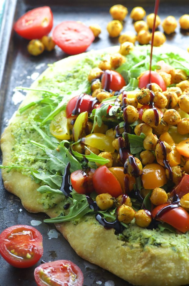 Side view of a ricotta pizza topped with tomatoes and spiced chickpeas and drizzled with a tangy pomegranate reduction.