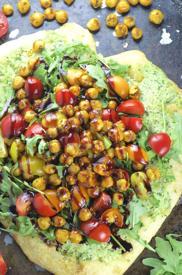 Topped with creamy cashew basil ricotta, arugula, tomatoes and spiced chickpeas and drizzled with a tangy pomegranate reduction, this Cashew Ricotta Pizza is like summer on a plate!