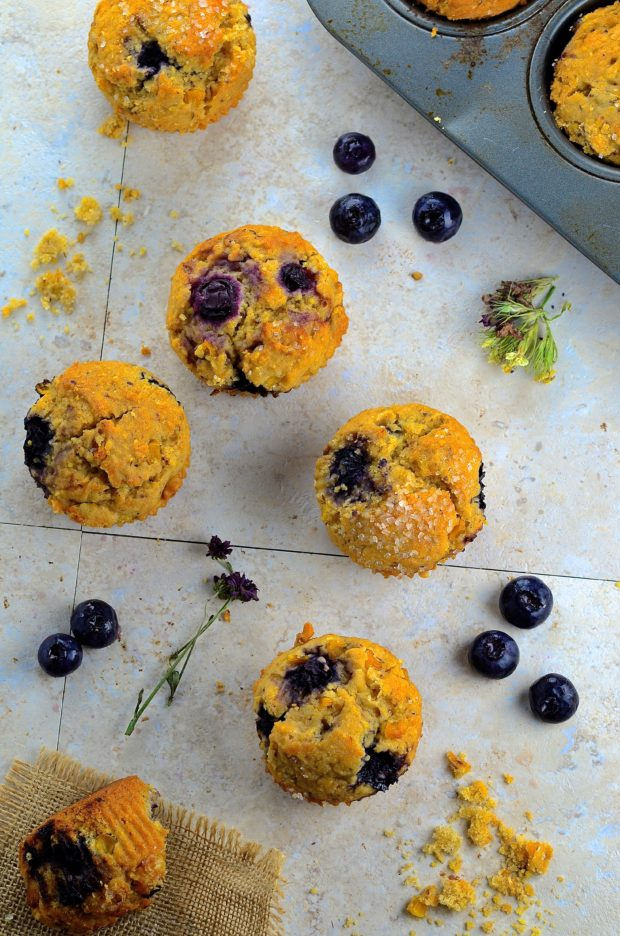 Bird's eye view of five Bluberry Corn Muffins on a white surface