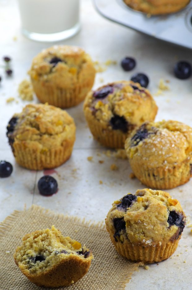 Side view of five Blueberry Corn Muffins on a white surface