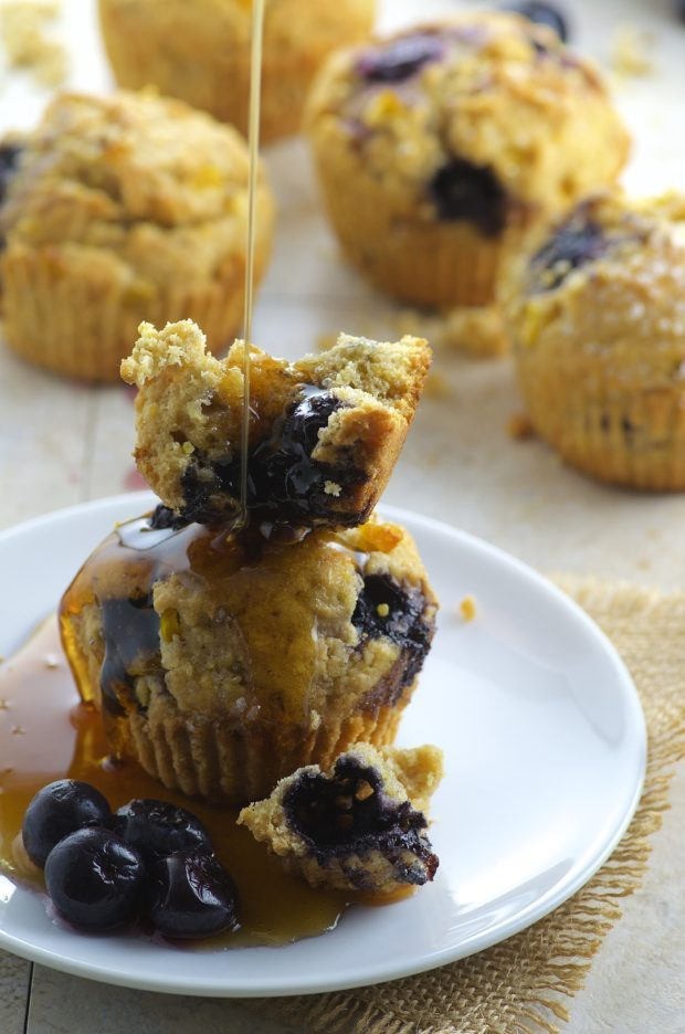Drizziling maple syrup on Bluberry Corn Muffins