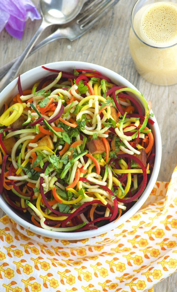 Bird's eye view of a bowl of spiralized beet, carrots and zucchini noodles with peanut sauce