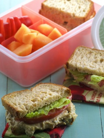 A chickpea spread sandwich cut in half with a container with cut up fruit in the background