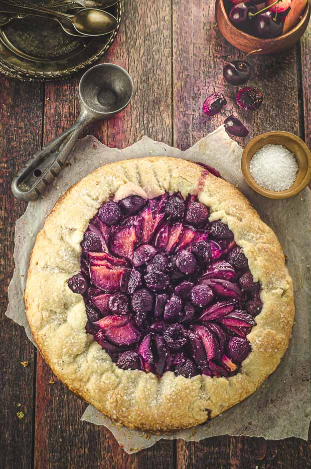 Bird's eye view of a summery stone fruit galette on a wood suface