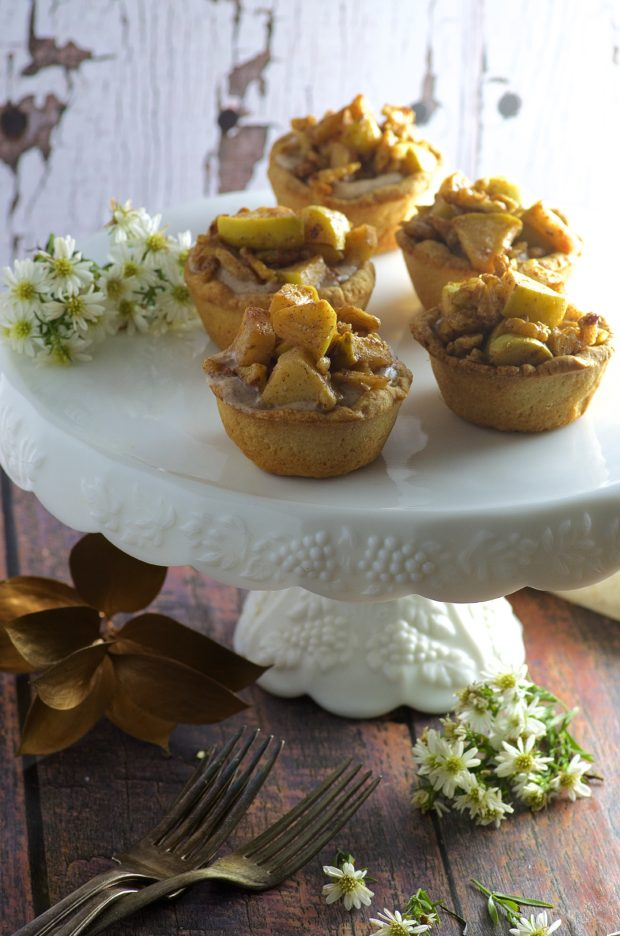 Bite Size Apple Pies, filled with sweet, rich cream cheese with a touch of cinnamon and maple syrup, topped with tart organic apples. The perfect little treat to welcome fall.