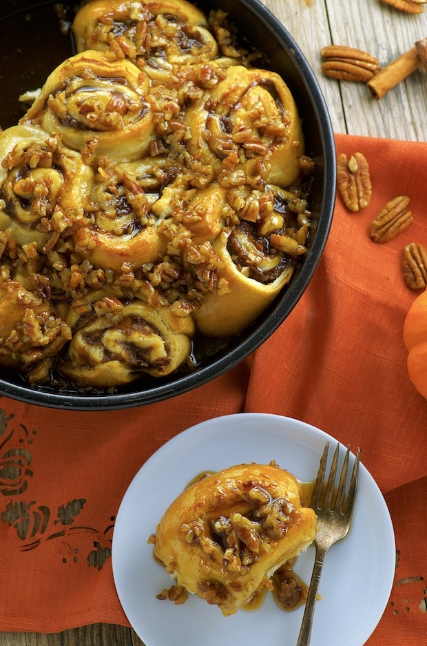 Birds eye view of Easy Banana Pumpkin Cinnamon Rolls on a round black metal baking dish. There is also a white plate with one pumpkin cinnamon roll on it and a small fork. The pumpkin cinnamon rolls are topped with maple syrup and pecans. The wooden surface where the pumpkin cinnamon rolls are placed on is partially covered with an orange napkin. On the napkin there are some pecan a couple sticks of cinnamon.