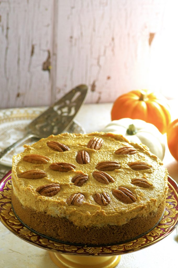 This Pumpkin Mousse Cashew Cheesecake is decorated with pecan halves.  The pumpkin mousse cheesecake is placed on a gold cake stand.  On the background there are some mini  pumpkins, a stack of plates and a metal cake spatula.